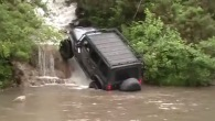 Off-Road 4x4 Jeep Drives up Through the Fierce Waterfall